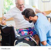 Pfleger kümmert sich um Patienten und hilft ihm aus dem Bett
