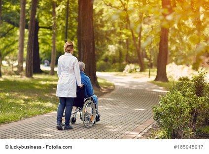 Pflegerin mit Patient im Rollstuhl im Park